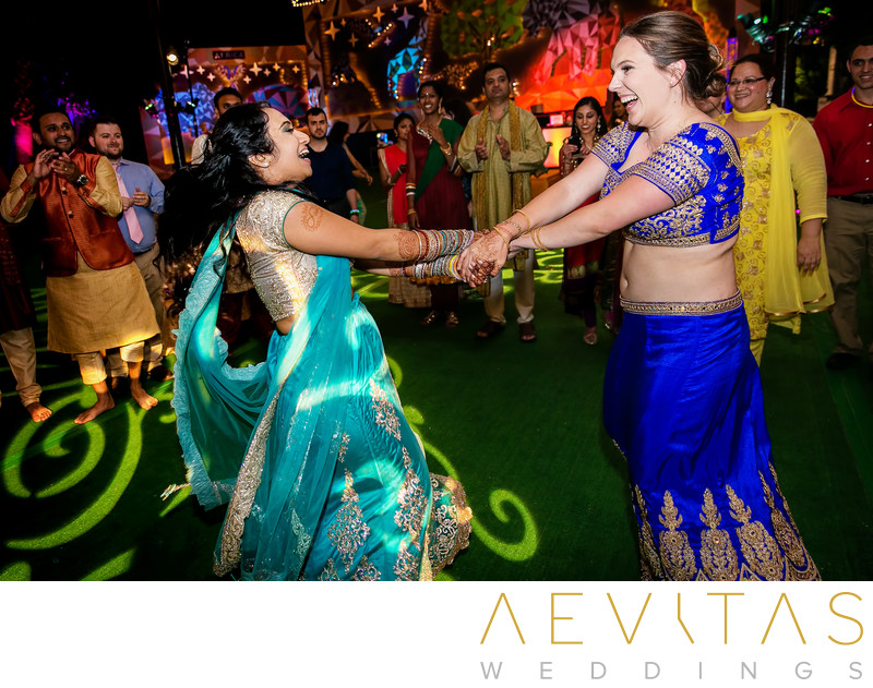 Bride and guest spinning at Indian wedding party