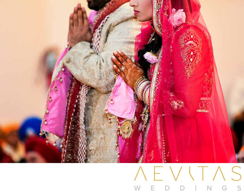 Photo of bride and groom praying at Sikh wedding