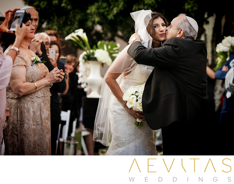 Bride kisses father at Jewish wedding ceremony in LA