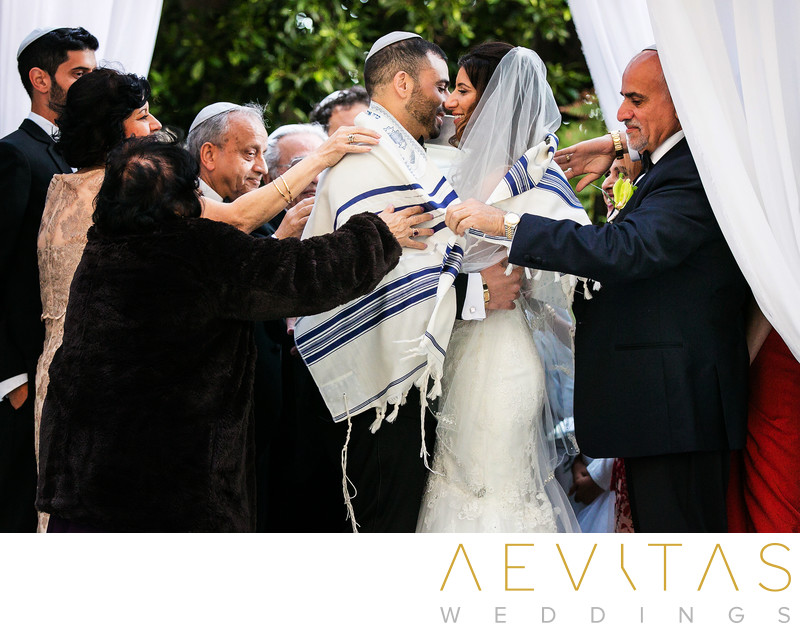 Couple covered by cloth at Jewish wedding in LA