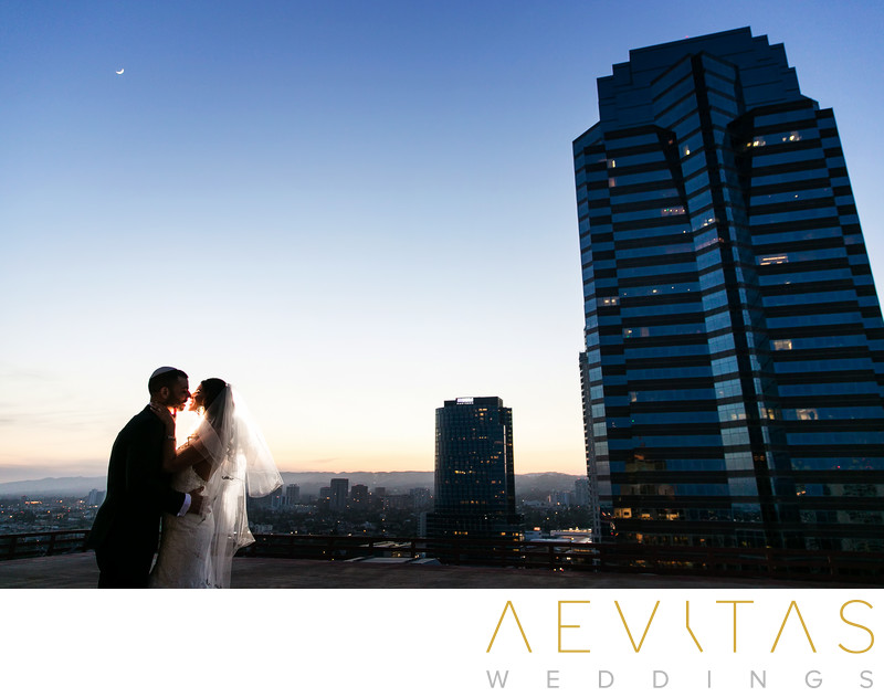 Couple kiss at sunset with skyscraper in Los Angeles