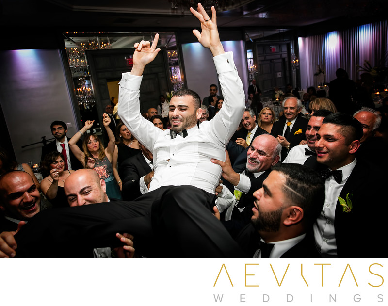 Groom lifted above dance floor at Jewish reception