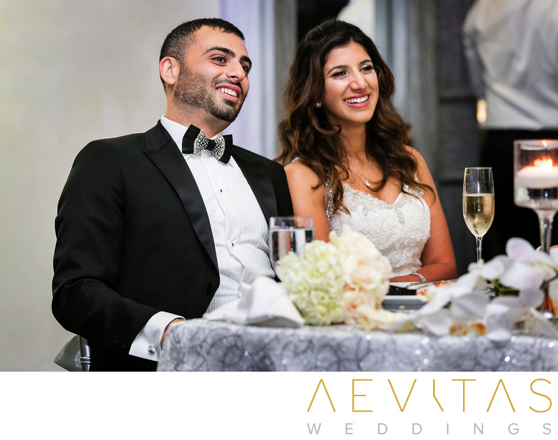 Bride and groom reactions at sweetheart table