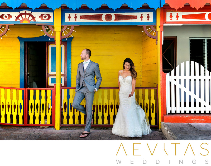 Bride and groom portrait with traditional Mexican house