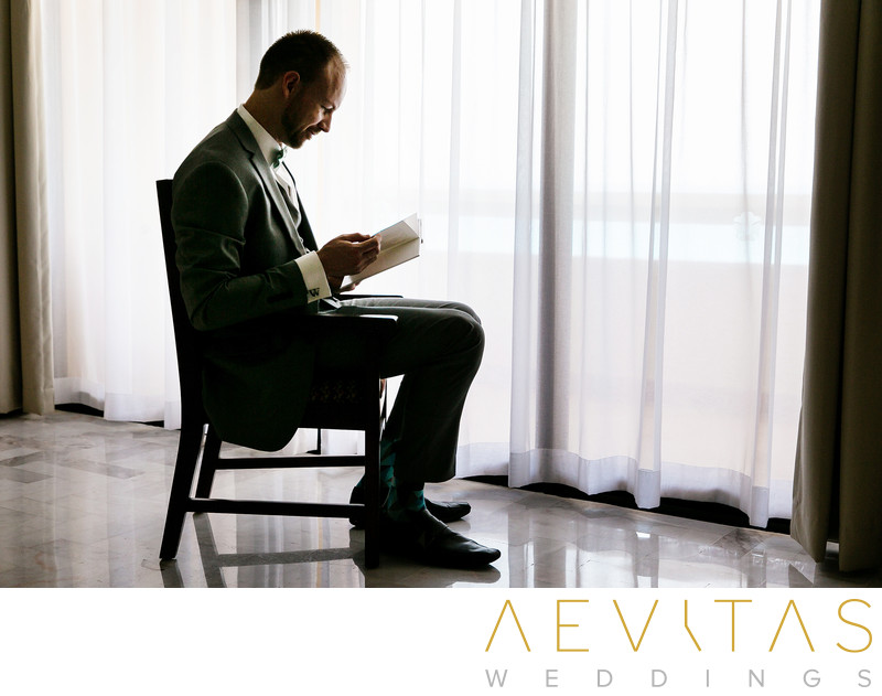 Groom reading at Omni Cancun Hotel And Villas