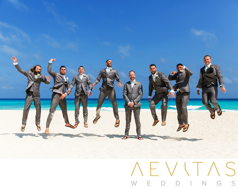 Groom and groomsmen jumping on Cancun white beach