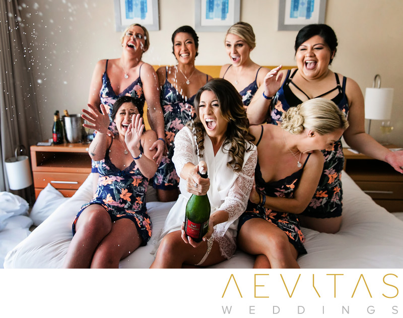 Bride pops bottle of champagne with bridesmaids