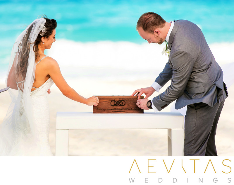 Bride and groom opening wooden box at Cancun wedding