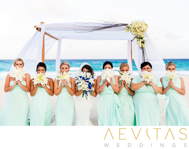 Bride and bridesmaids hiding behind bouquets in Cancun