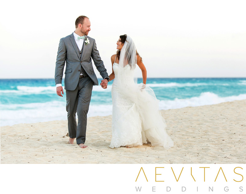 Bride and groom walking along white beach in Cancun