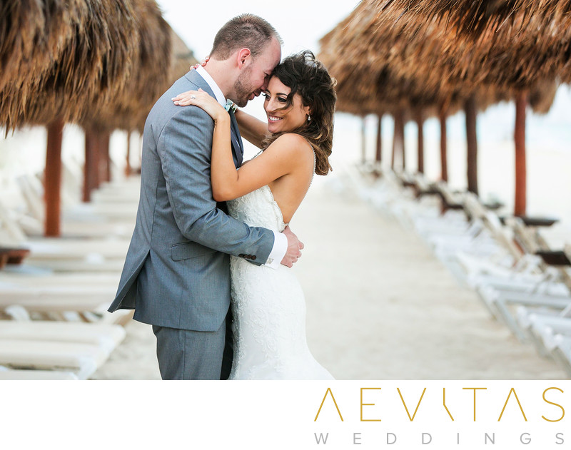 Couple embrace between beach umbrellas in Cancun
