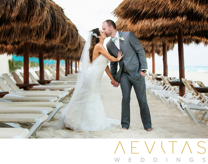 Bride and groom kiss between thatched beach umbrellas