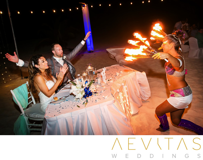 Couple at sweetheart table with fire dancer in Cancun