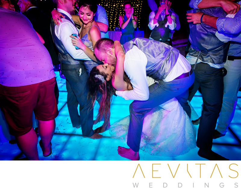Groom dips and kisses bride on colorful dance floor