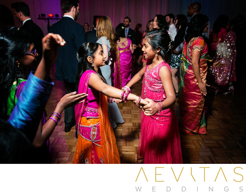 Young wedding guests dancing at Indian reception