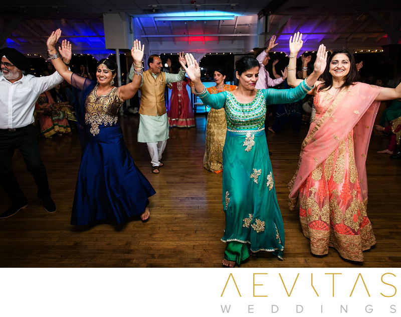 Family dancing with hands in air at Indian wedding