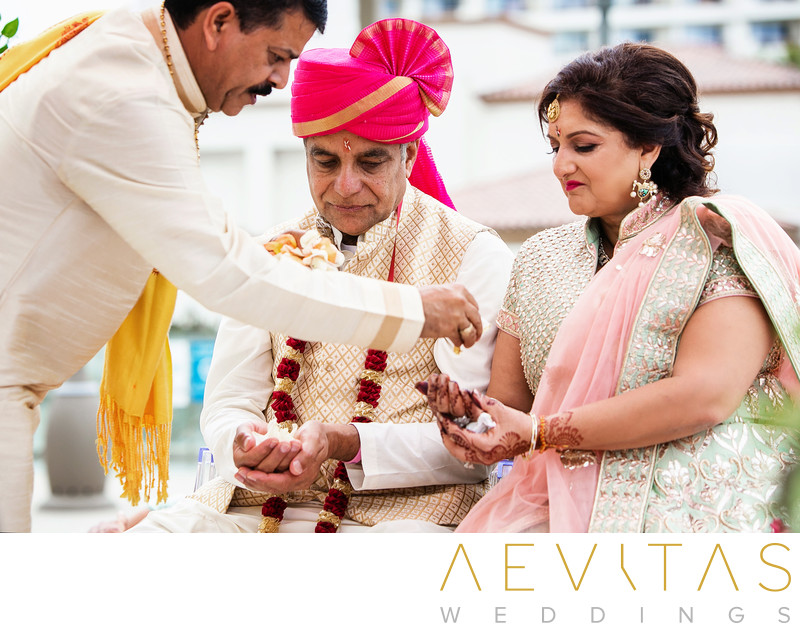 Officiant gives flower petals to parents Indian wedding