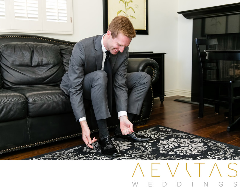 Groom tying shoelace at Rolling Hills Estates residence