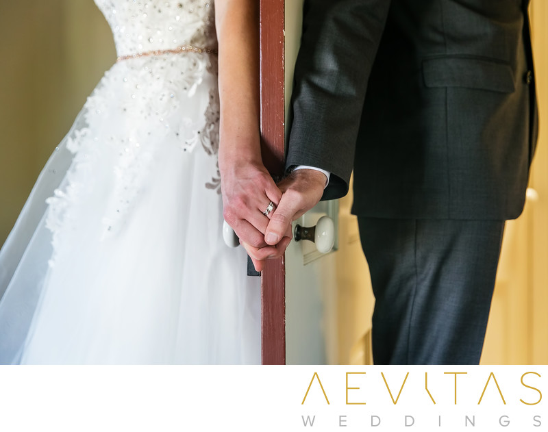 Close-up photo of bride and groom holding hands