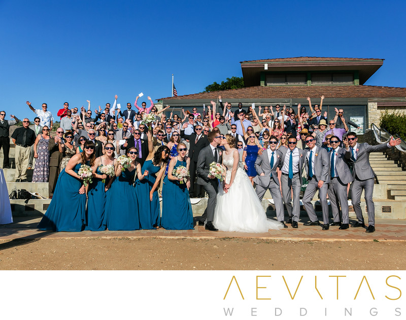 Couple kiss with wedding party at Point Vicente