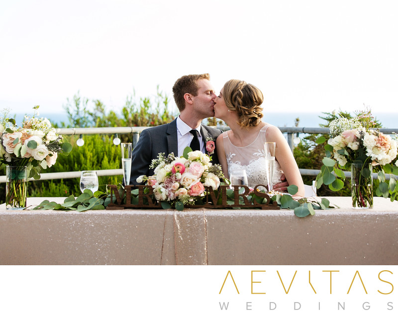 Couple kiss at Point Vicente wedding sweetheart table
