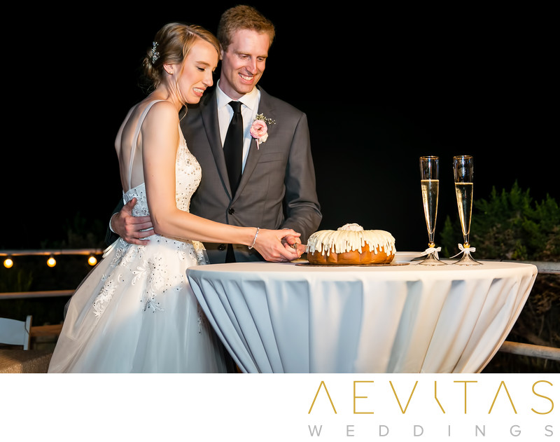 Couple cutting wedding cake at Point Vicente reception