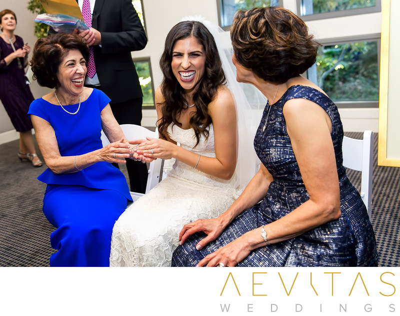 Bride laughing with moms at Skirball Bedeken ceremony