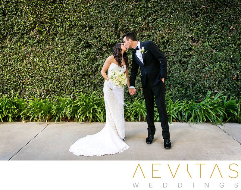 Couple kiss with hedge at Skirball Cultural Center