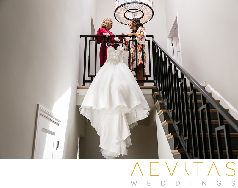 Bride with mom and dress beside staircase in LA