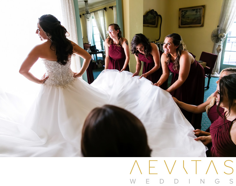 Bridesmaids holding bride's dress at The Ebell of LA