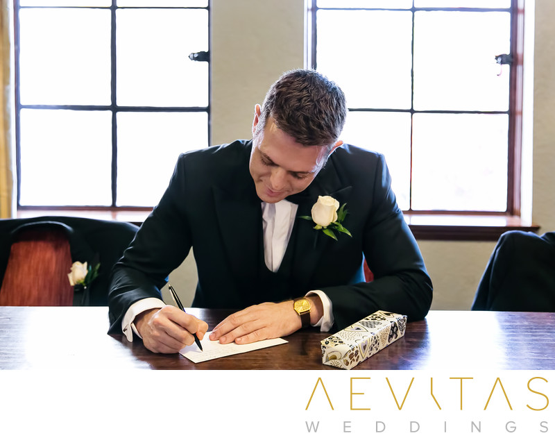 Groom writing card to bride at The Ebell of Los Angeles