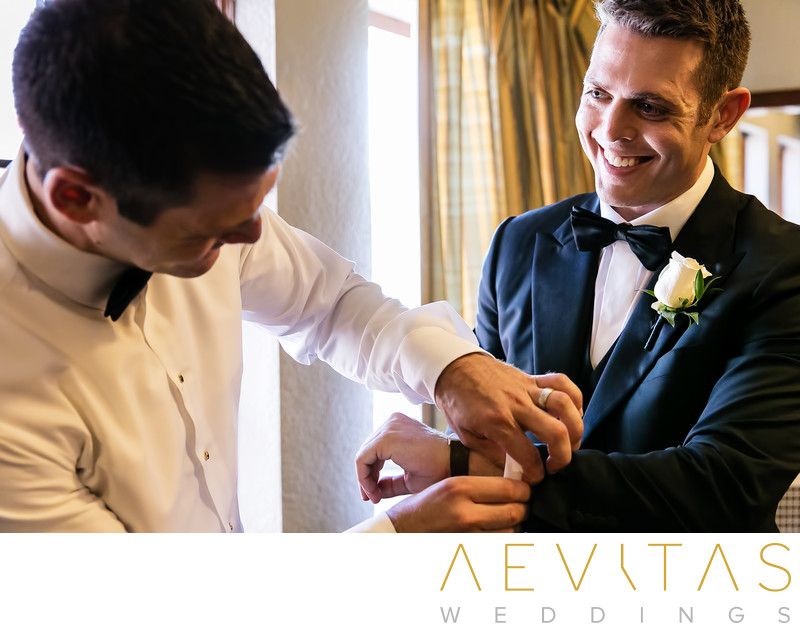Best man putting on groom's cufflinks at LA wedding