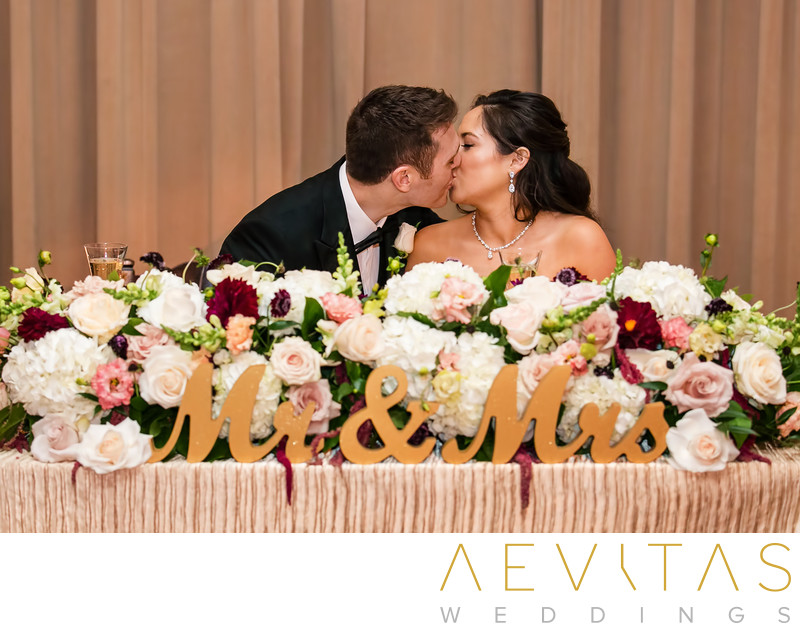 Couple kiss at Ebell Los Angeles sweetheart table