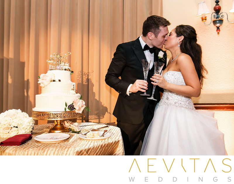 Couple kiss with wedding cake at The Ebell of LA