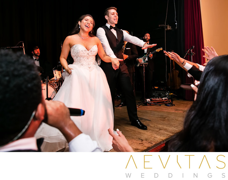 Couple sing to wedding guests on stage at The Ebell LA