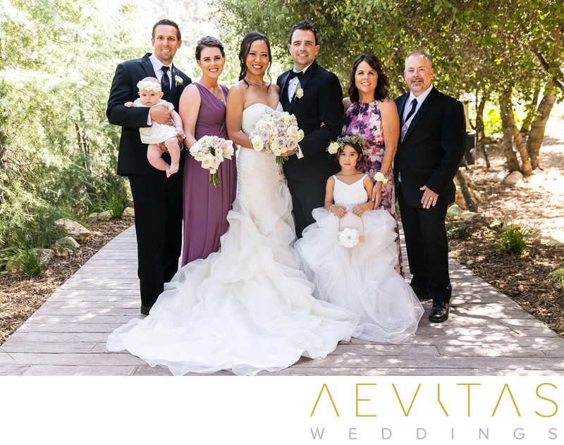 Couple portrait with groom's family at Oak Glen wedding