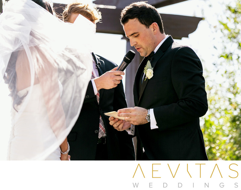 Groom reading vows with bride's veil Oak Glen wedding