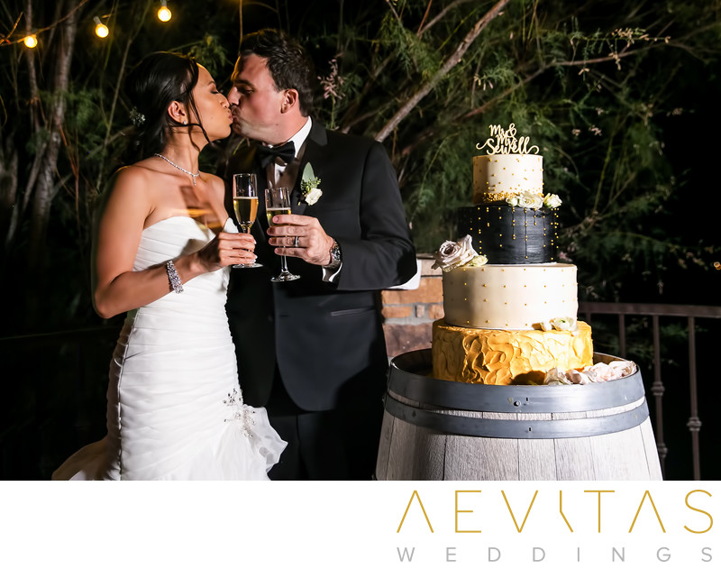 Couple kiss with champagne and wedding cake in Oak Glen