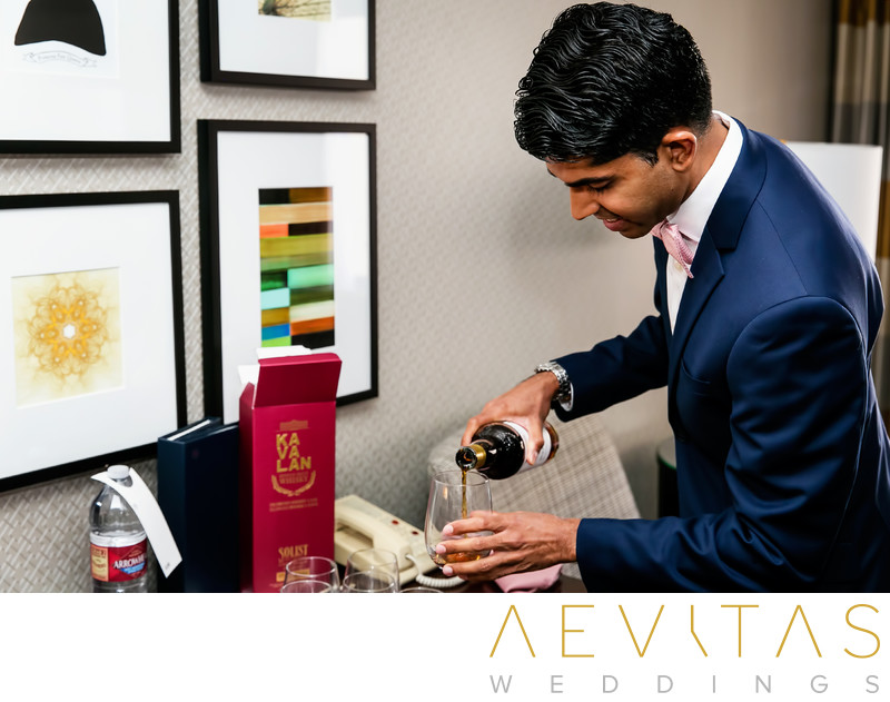 Groom pouring whiskey in Pomona hotel suite