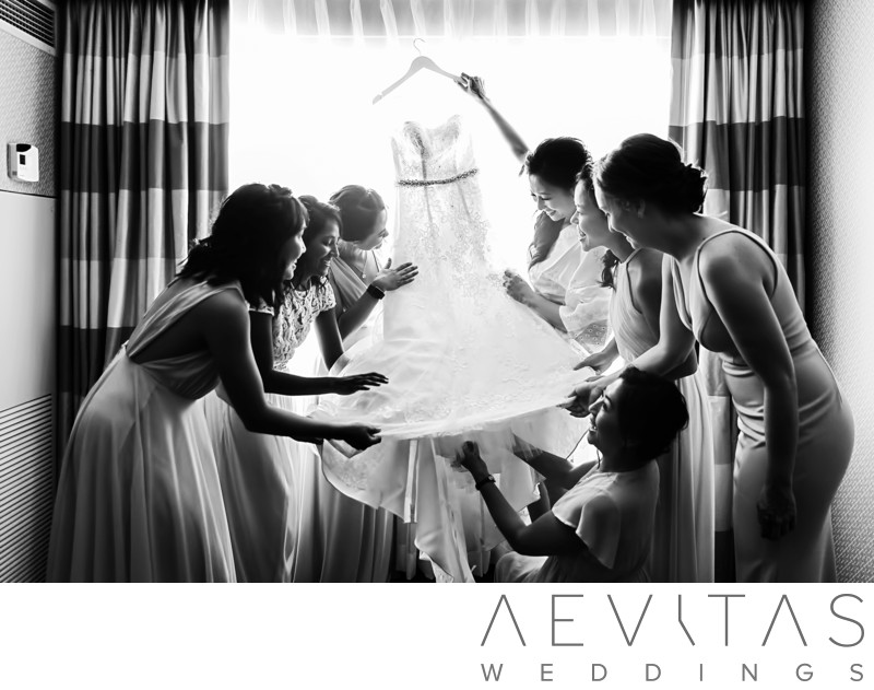Black and white photo bridesmaids admire wedding dress