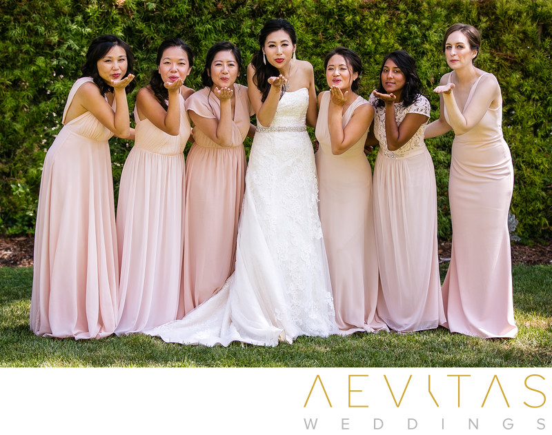 Bridesmaids blowing kisses in Pomona hotel gardens