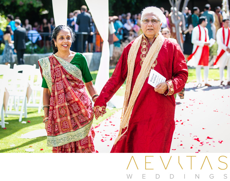 Groom's parents walking down aisle at Indian wedding