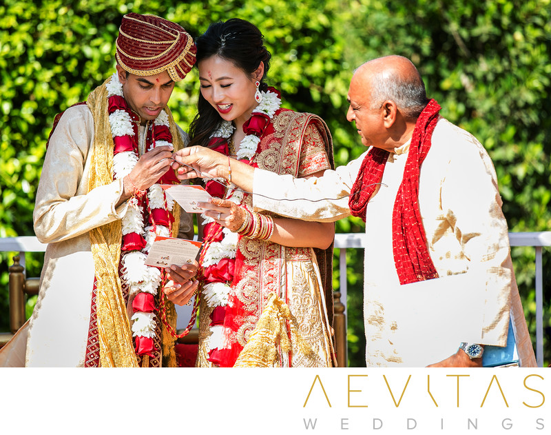 Couple reading with officiant at Hindu wedding ceremony