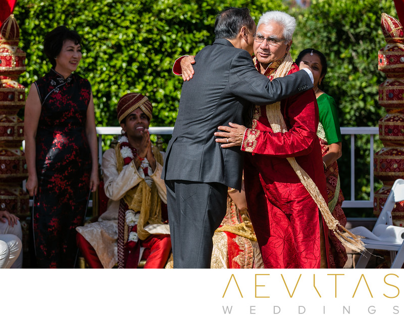 Fathers embrace at Pomona multicultural wedding