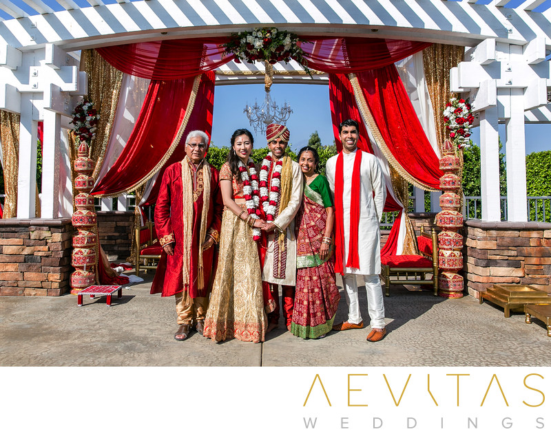 Couple with groom's family on mandap stage in Pomona