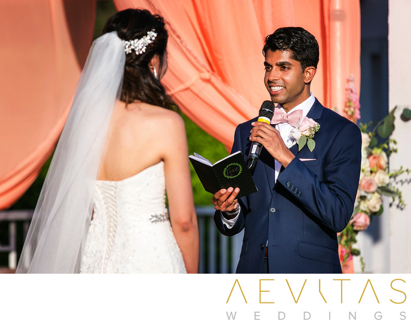 Groom smiling while reading vows at Pomona wedding