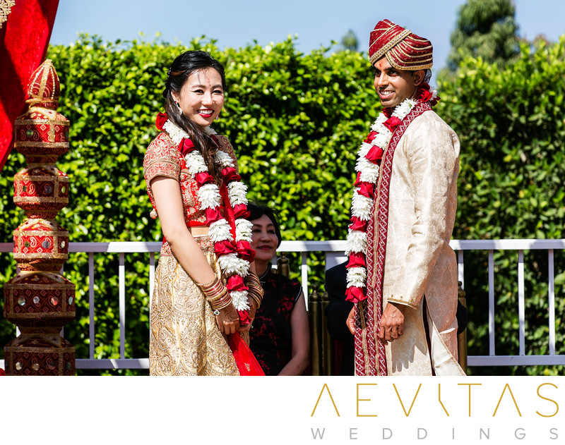 Couple smiling at guests with garlands Indian wedding