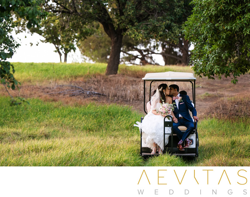 Couple kiss in back of golf cart at Pomona wedding