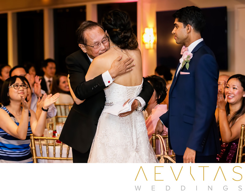 Bride embraces father at Pomona wedding reception