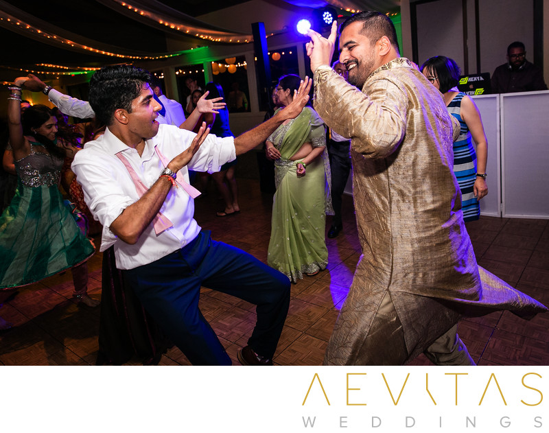 Groom and friend dancing at Indian wedding party